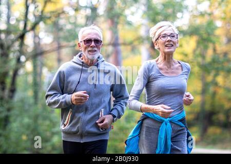 un par de pensionistas corriendo en el parque