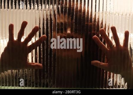 Imagen espeluznante de la niña detrás del cristal con las palmas de las manos sobre el cristal texturizado