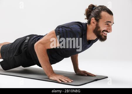 Imagen de alegre deportista de morena en chándal sonriendo mientras entrena en una alfombrilla de yoga aislada sobre fondo blanco Foto de stock