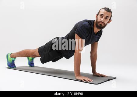 Imagen de hombre morena deportista en traje de pista haciendo ejercicio sobre colchoneta de yoga aislada sobre fondo blanco Foto de stock