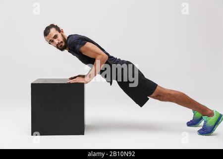 Imagen de un deportista de morena masculina en chándal haciendo flexiones desde un cubo de entrenamiento negro aislado sobre fondo blanco Foto de stock