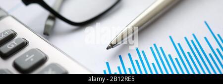 Pluma de Plata con papel gráfico y gafas se encuentran en mesa de oficina