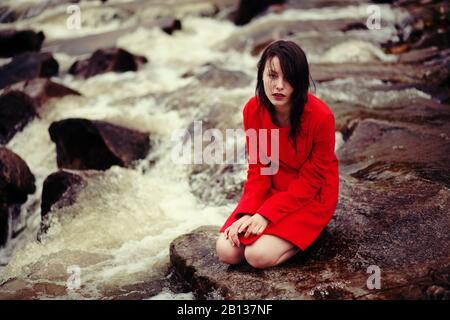 Mujer joven está sentado sobre un arroyo