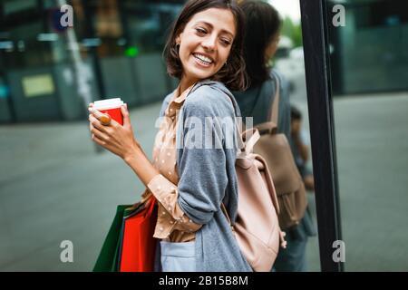 Feliz mujer joven bebiendo tomar café y caminar con bolsas después de ir de compras en la ciudad.
