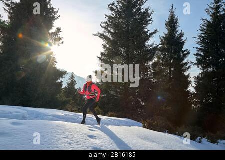Corredor en chaqueta rosa mujer corriendo en invierno montaña camino en la nieve.
