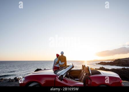 Pareja disfrutando de hermosas vistas sobre el océano, abracándose cerca del coche en la costa rocosa, amplia vista desde el lado con espacio para copias en el cielo