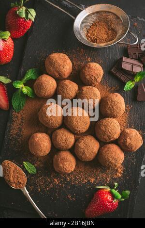 Trufas De Chocolate Negro Caseras Recubiertas En Polvo De Cacao Sobre Fondo De Pizarra Negro. Sabrosas Dulces De Chocolate Caseros