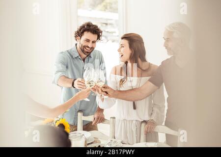 Familia y amigos que almorzan juntos y que se clinking copas de vino