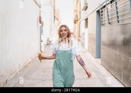 Retrato de una joven feliz con helado cono caminando a lo largo de un callejón Foto de stock