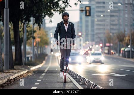 Retrato de un hombre de negocios montando una scooter en el carril de la bicicleta por la noche