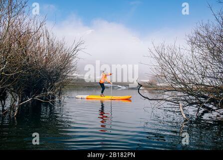 Mujer de pie remar surfing en un lago
