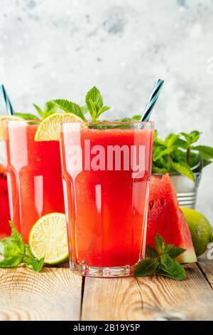 Sandía sluhie con cal y menta, bebida refrescante de verano en vasos altos sobre un fondo azul claro. Batido frío dulce