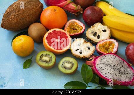 Fruto de fondo. Surtido de frutas de temporada de verano exóticas asiáticas jugosas maduras sobre un fondo de piedra azul. Espacio de copia.