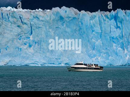 PARQUE Nacional LOS GLACIARES, ARGENTINA - ALREDEDOR DE FEBRERO 2019: Barco con turistas navegando por las aguas del Lago Argentino en el Glaciar Perito Moreno, A.