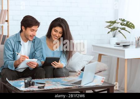 Planear las finanzas. Pareja preparándose para vacaciones y calculando gastos