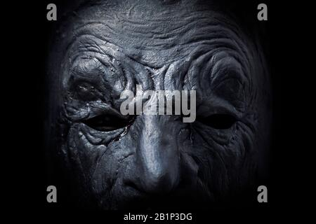 Figura aterradora con máscara en la fotografía macro y oscura