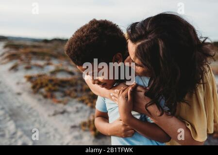 Vista lateral primer plano retrato de una joven madre abrazando la playa de son