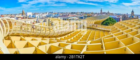 Sevilla, ESPAÑA - 1 DE OCTUBRE de 2019: El puente peatonal curvo conduce a lo largo de los bordes del techo del complejo Metropol Parasol y abre magníficas vistas de toda la sid