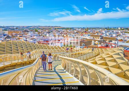 Sevilla, ESPAÑA - 1 DE OCTUBRE de 2019: Los turistas caminan a lo largo del puente peatonal de Metropol Parasol disfrutando de unas vistas increíbles de la arquitectura circundante, 1 de octubre i