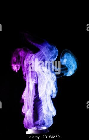 Nubes de color de humo de la vape. Muchas nubes de color y glicerina, colores rojo y azul. Foto de stock aislada sobre fondo negro con aerosol boling o
