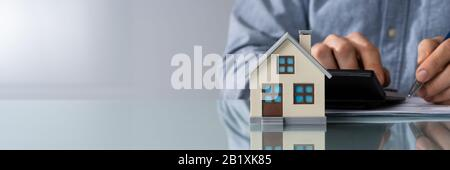 Close-up de la mano de una persona haciendo Cálculo de impuestos de propiedad con la Calculadora de casa modelo Foto de stock