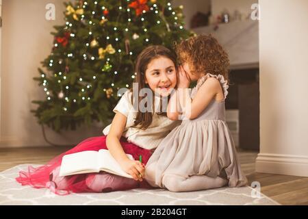 Dos niñas en un piso en la víspera de Navidad