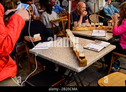 Brujas, Bélgica. Agosto De 2019. Degustación de cervezas artesanales belgas: Doce tazas dispuestas en el portavasos de madera. La gente está sentada en las mesas disfrutando