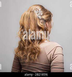 Rizos de onda peinado. Peinado sobre rubio con pelo largo sobre fondo blanco. Peluquería profesional Services.Hair peinado, fabricación