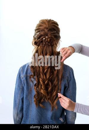 Rizos de onda peinado. Peluquería haciendo el peinado a la mujer de pelo marrón rojo con el pelo largo usando el peine en fondo blanco. Peluquería profesional