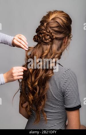 Rizos de onda peinado. Peluquería haciendo el peinado a la mujer de pelo marrón rojo con el pelo largo usando el peine en fondo gris. Peluquería profesional