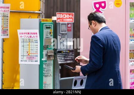 Kyoto, Japón - 17 de abril de 2019: Calle de la ciudad en el centro de la ciudad con el hombre comprando en el estacionamiento cerca de la máquina expendedora que cantaba a la gente local persona salaryman