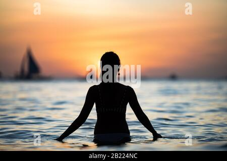 Silueta de una niña admirando una impresionante puesta de sol en la playa blanca de Boracay. La playa blanca de Boracay está situada en la estación 1. Foto de stock