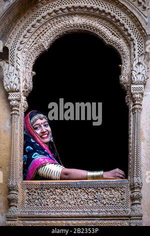 Chica mirando por una ventana de un haveli viejo, Jaisalmer, Rajasthan, India Foto de stock