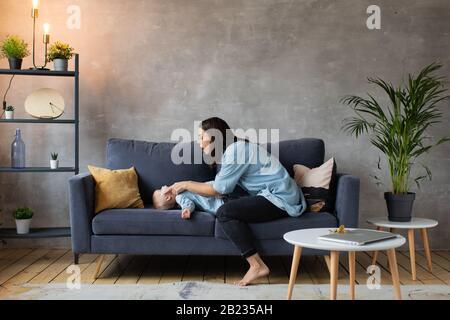 Madre joven Jugando con niños en el sofá. Familia feliz. Comodidad en el hogar. Foto de stock