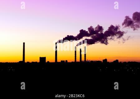 Mala calidad del aire. Contaminación del aire en la fábrica. Humo de la chimenea de la tubería industrial en el cielo de la puesta de sol. Concepto del problema del calentamiento global.