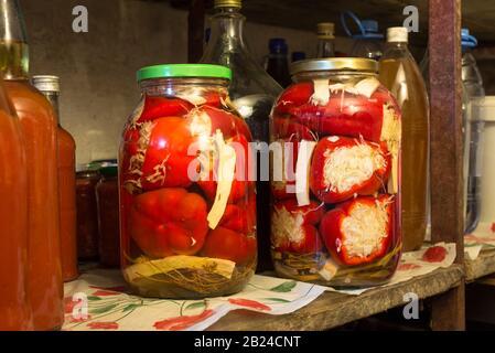 Botellas de vidrio con pimientos picados caseros en una estantería de una bodega en Hungría