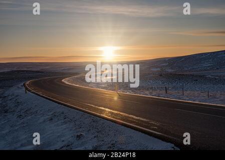 Islandia carretera en la puesta de sol de invierno