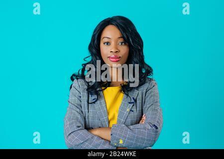 Retrato de una joven en chaqueta de negocios con los brazos cruzados aislados en azul