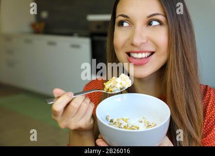 Primer plano de la hermosa mujer joven comiendo yogur Skyr con cereal muesli fruta en casa, mirando al lado, foco en los ojos modelo, imagen de interior. H