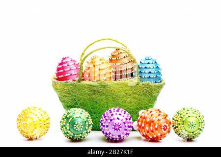 Símbolo de Pascua en color verde cerca de huevos con cuentas. Feliz concepto de vacaciones. Decoración de Pascua: Cesta con colección de huevos pintados y decorados. Cesta llena de huevos de Pascua aislados sobre fondo blanco.