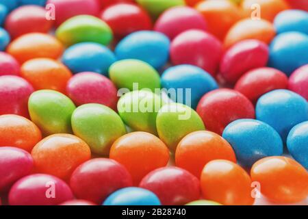 Colores arcoiris de primeros planos de caramelos multicolores, textura y repetición de dragados Foto de stock