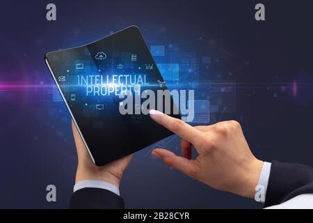 Empresario sosteniendo un smartphone plegable con la inscripción de la propiedad intelectual, el concepto de seguridad cibernética