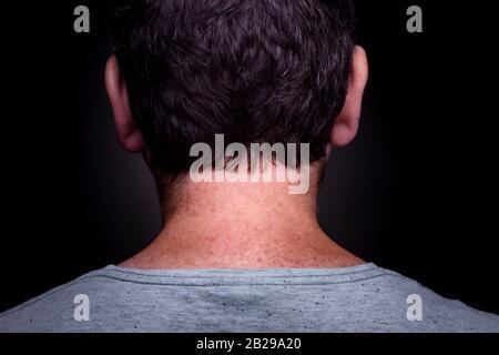 Macho caucásico anónimo con pelo marrón corto y camisa verde gris y pecas en su cuello visto desde atrás contra un fondo oscuro