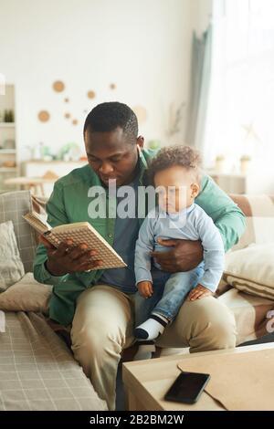 Retrato vertical de un hombre africano-americano maduro leyendo un libro al niño sentado en el regazo de los padres