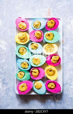 Huevos duros de colores tradición pascual, huevos teñidos naturalmente para las vacaciones de pascua con ingredientes naturales, vista superior composición plana