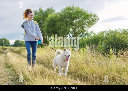 Estilo de vida activo y saludable, niña que camina con perro husky blanco