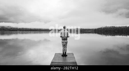 Hombre joven de pie en un embarcadero con vistas a un lago, ambiente foggy, Lago Mapourika, Costa Oeste, Isla Sur, Nueva Zelanda