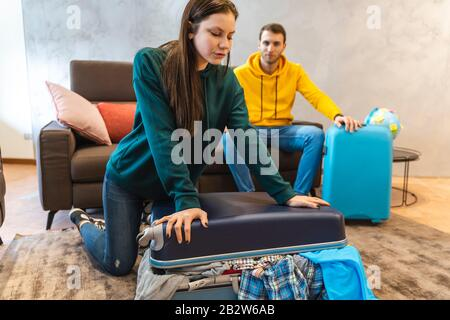 pareja joven está preparando las maletas para el próximo viaje en la sala de estar en casa. vacaciones alrededor del mundo concepto