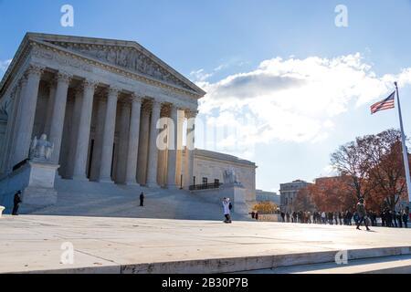 Corte Suprema de los Estados Unidos en el soleado día en D.C. con la bandera de los Estados Unidos agitando bajo la luz del sol.