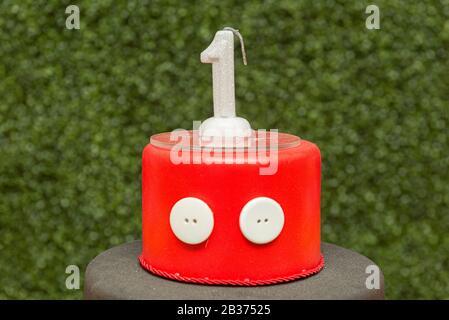 parte superior de pastel falso rojo con una vela en forma de una vela con fondo verde borroso. Celebración blanca de un año con. Conc. De la fiesta de cumpleaños de los niños